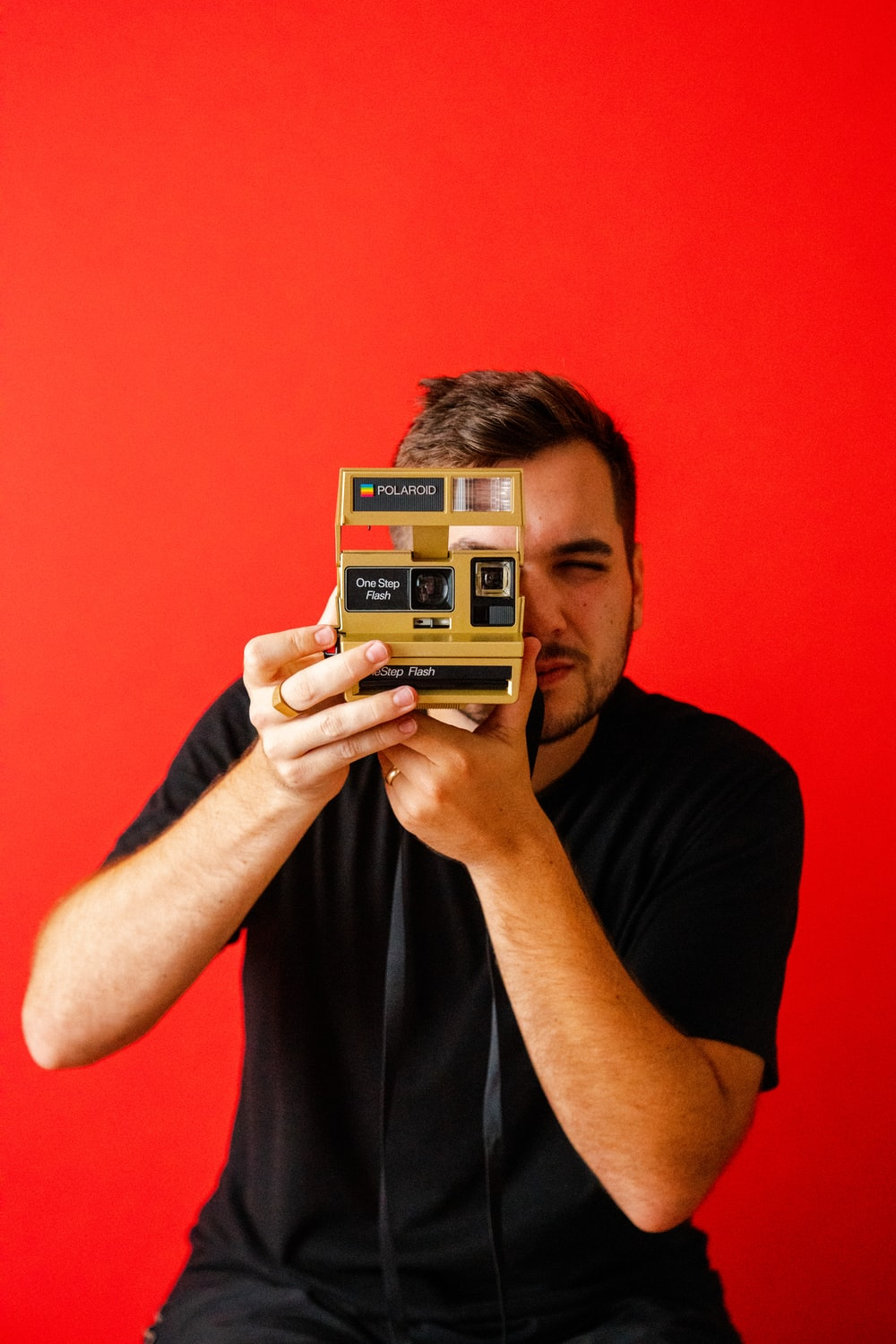 man holding vintage brown and black instant camera