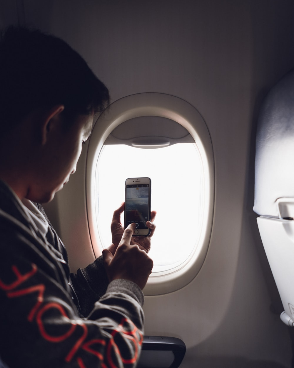 man using smartphone sitting beside airplane window
