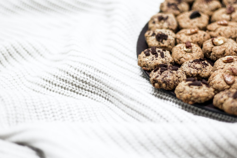 plate of baked chocolate cookies on white tablecloth