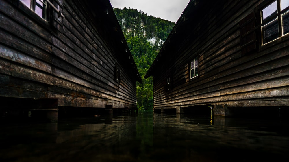 two wooden buildings in body of water
