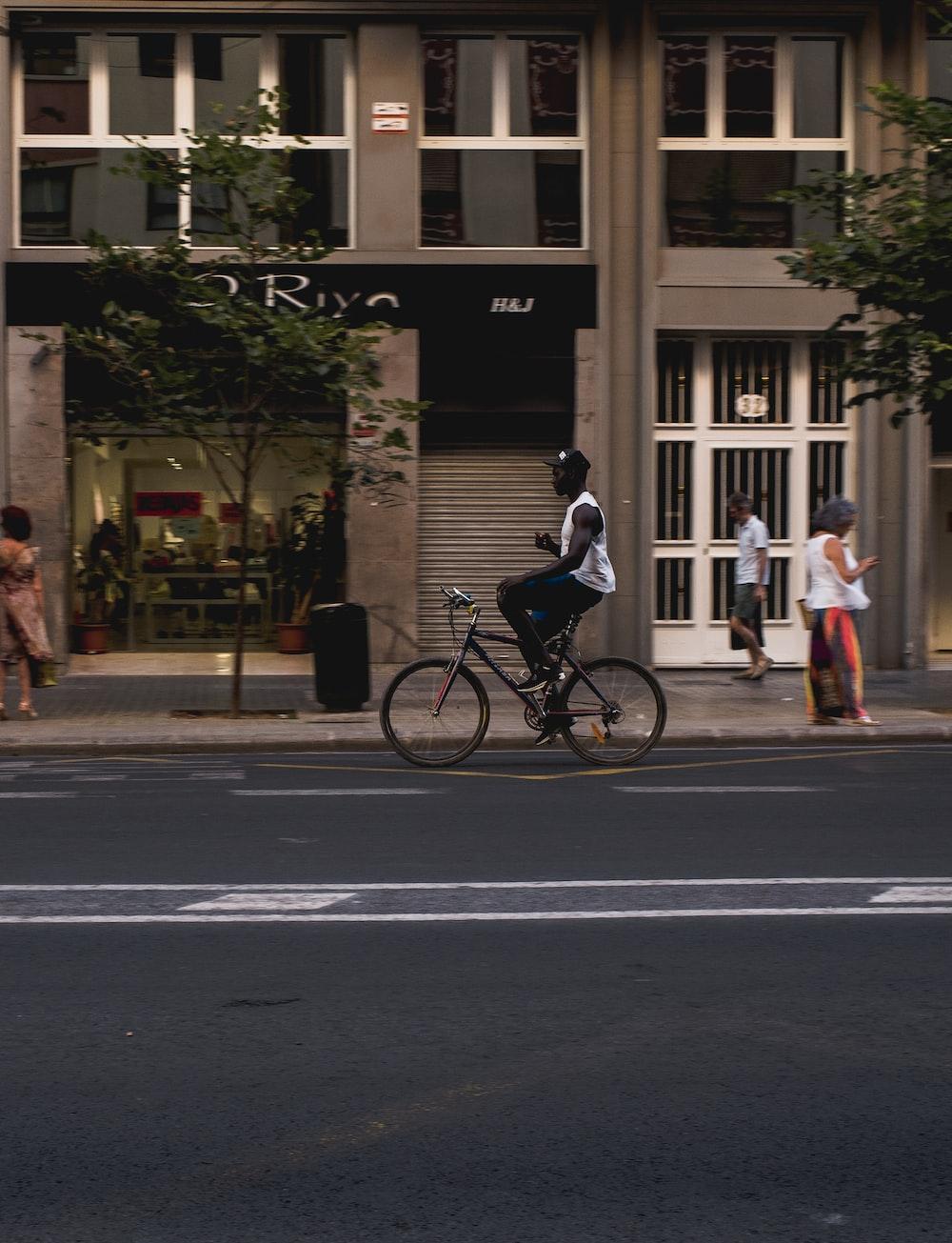 man on black bike in street