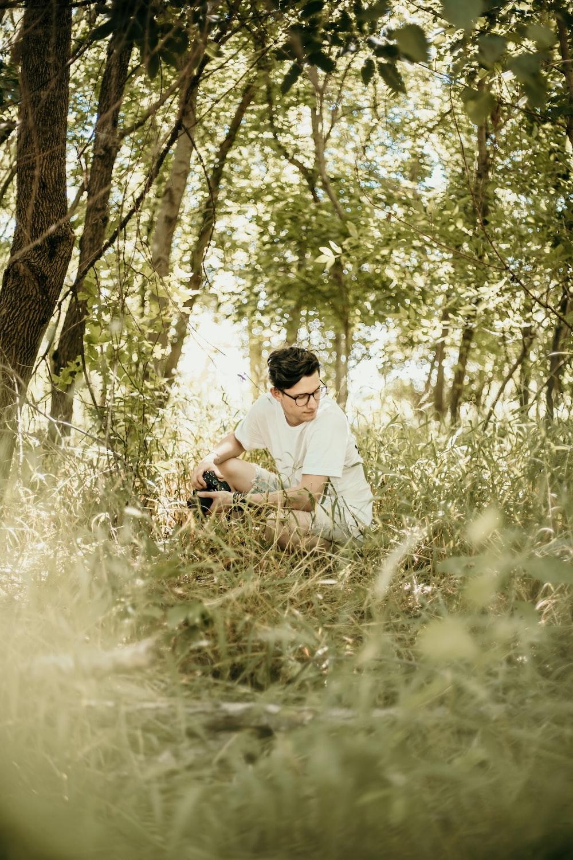 man sitting near green-leafed trees