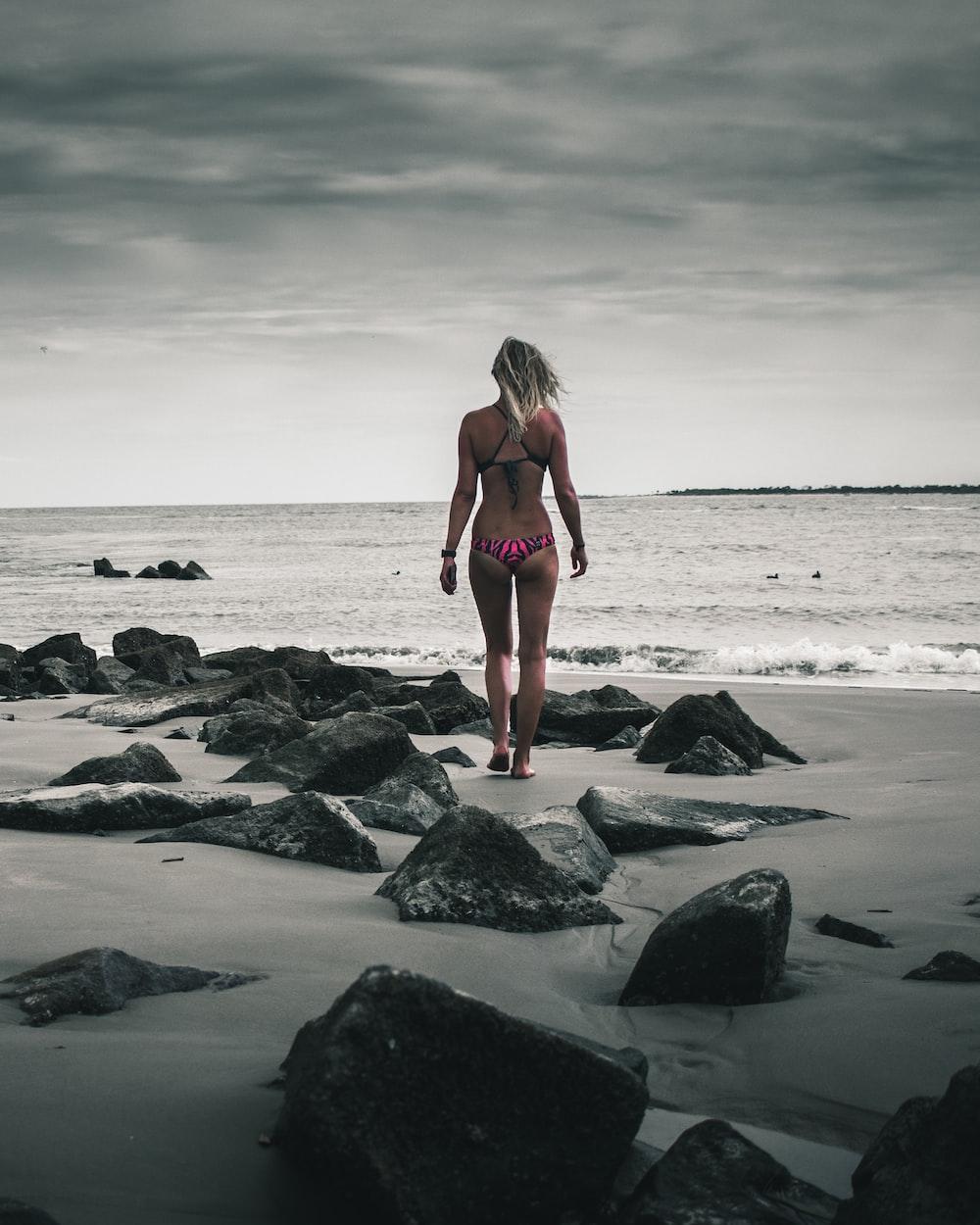 woman in pink bikini standing in rocky beach