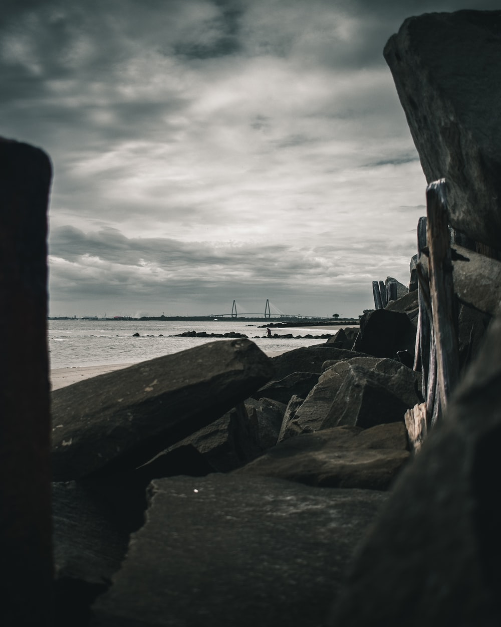 boulders facing ocean under cloudy sky