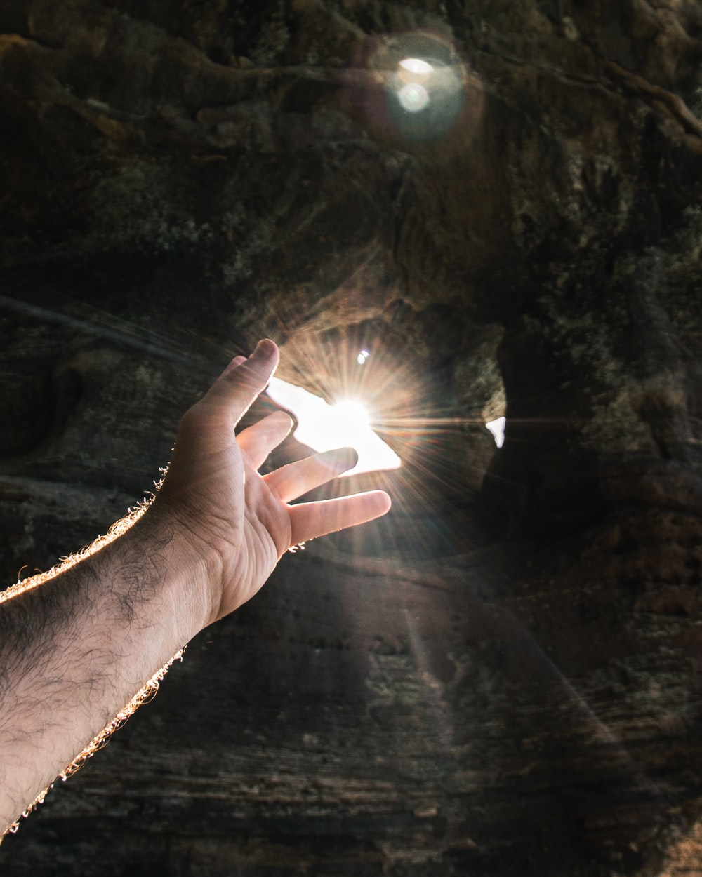 person pointing on sun rays
