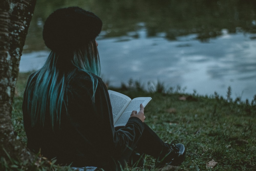 woman holding book while sitting near green field beside lake