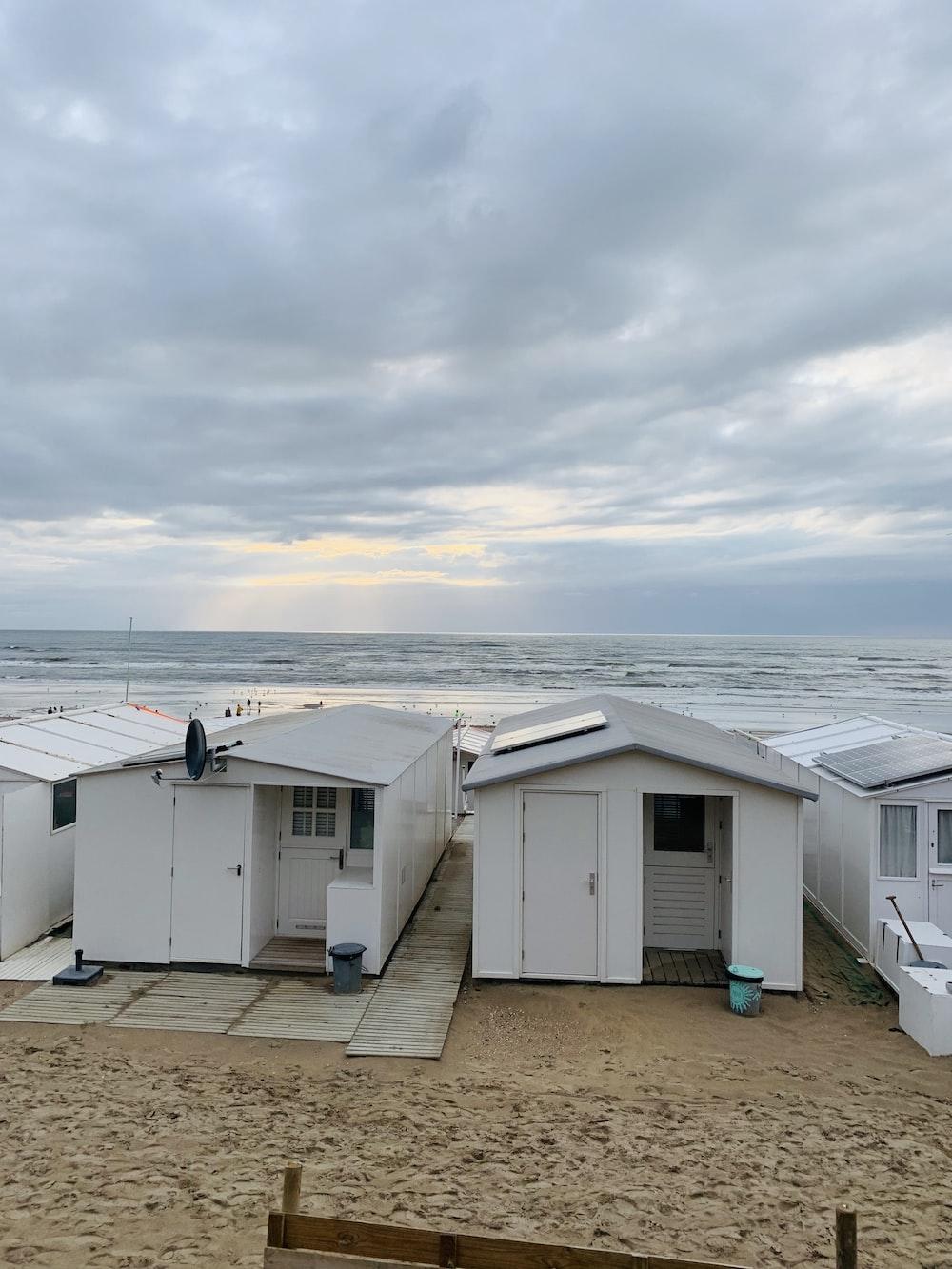 white houses near ocean under cloudy sky