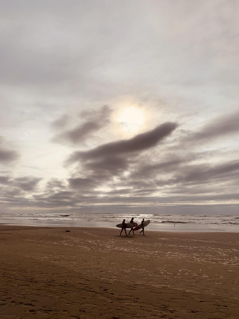 three people holding surfboard walking near seashore