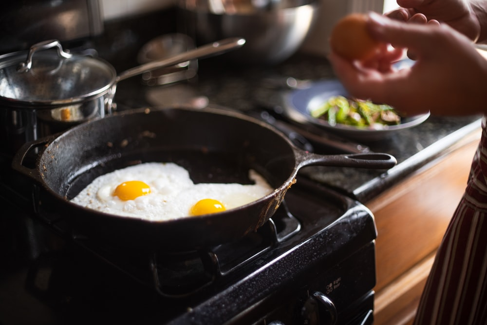 food photography of two fried eggs on cast-iron skillet