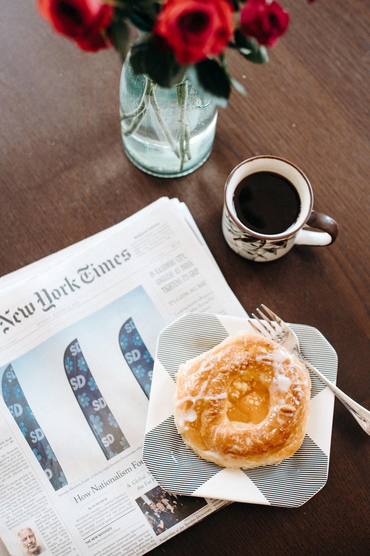 baked bread on plate near mug with coffee