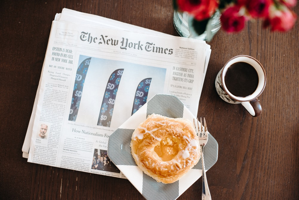 The New York Times paper on a brown table