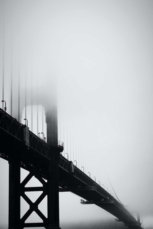 grayscale photography of bridge under fog