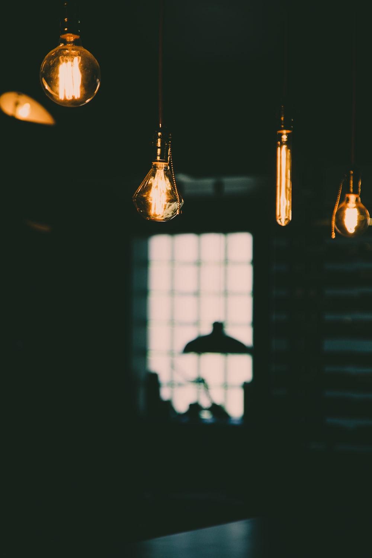 four turned-on yellow Edison light bulbs