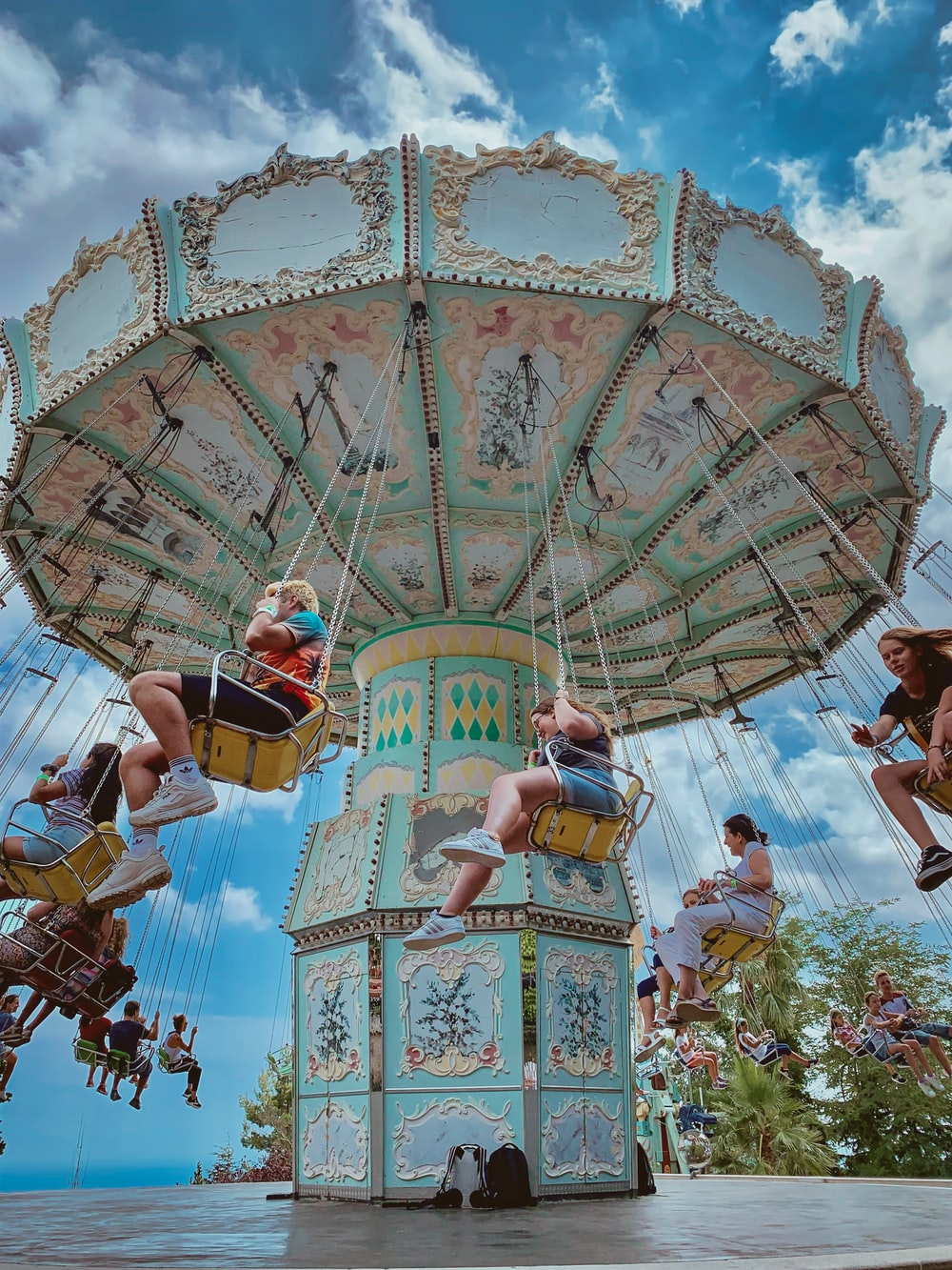 people riding on merry-go-round during daytime
