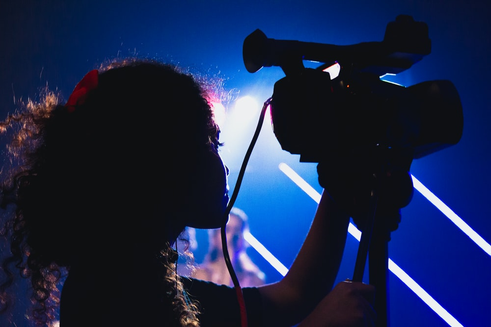 silhouette photography of woman holding a video camcorder