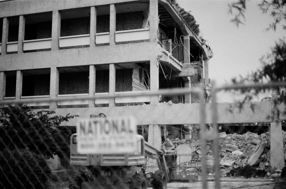 grayscale photo of white and gray 3-storey building