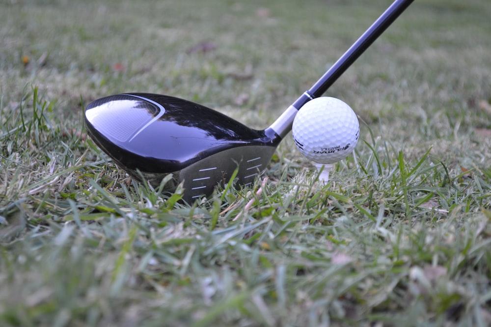 white golf ball beside black and gray golf