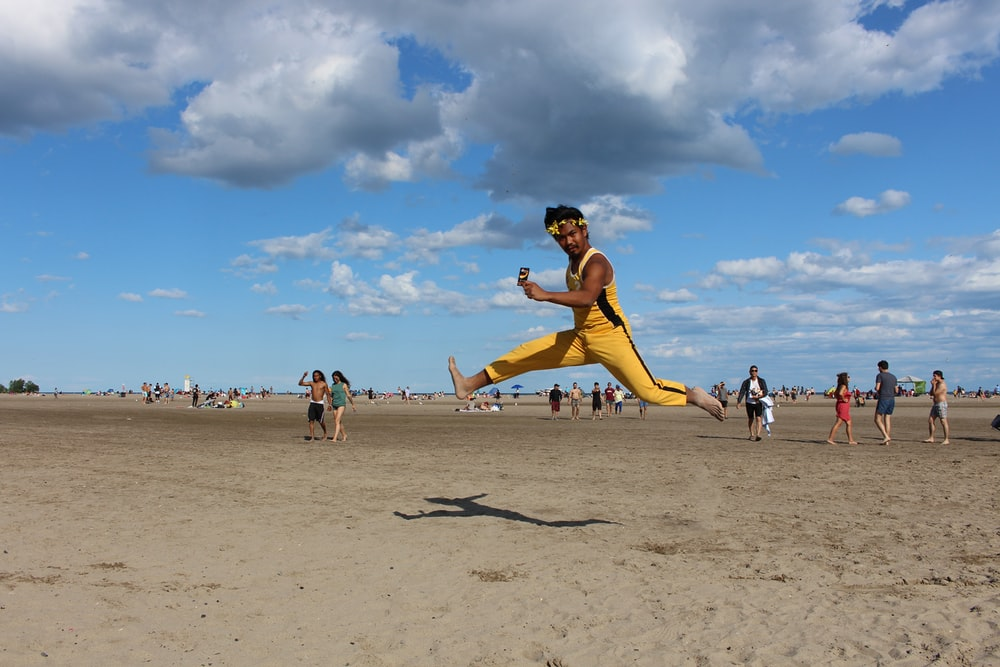 man jumping on seashore