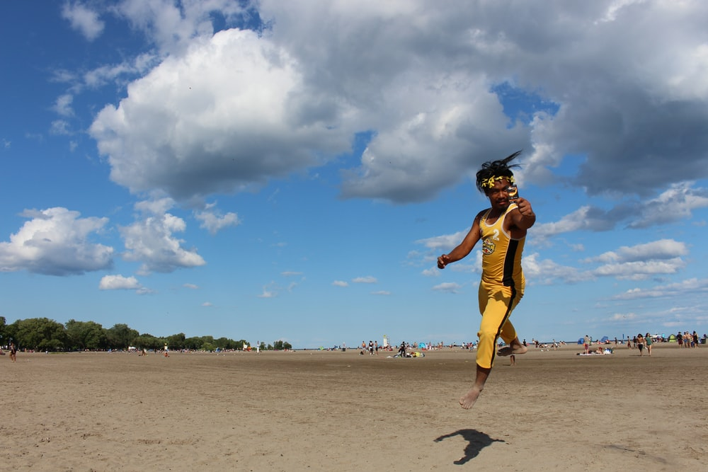 man wearing yellow-and-black tracksuit about to jump on brown sand