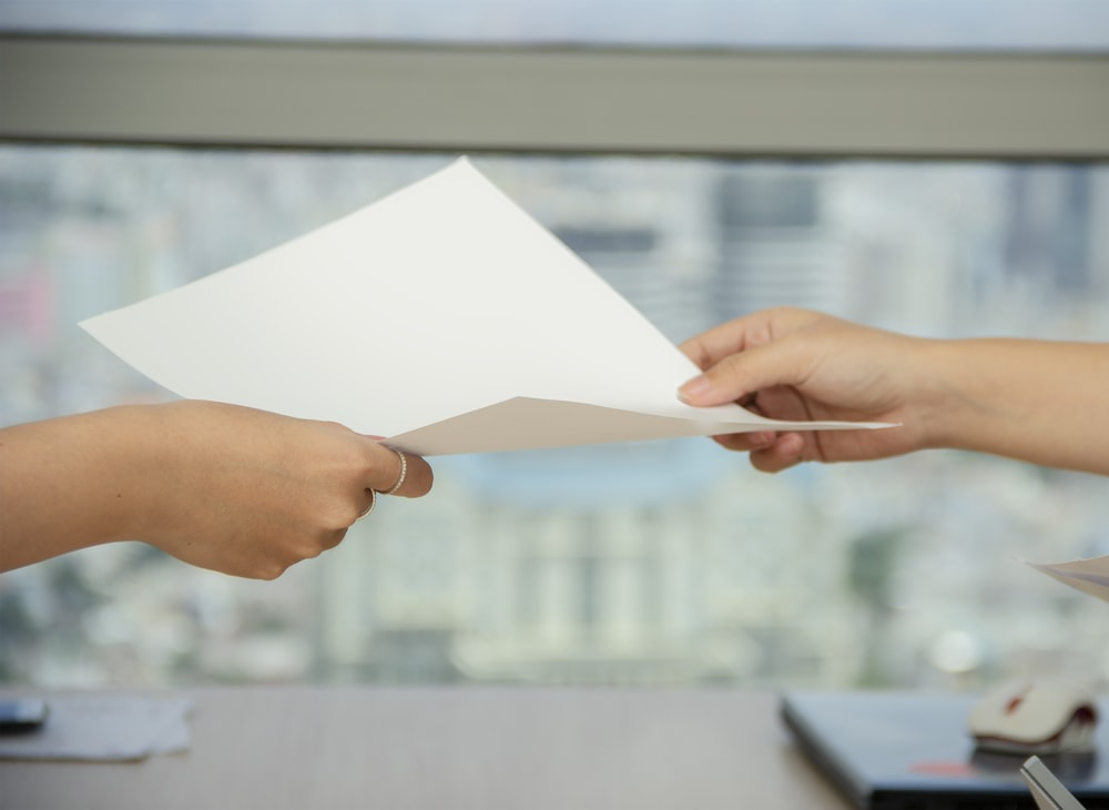 person handing over paper