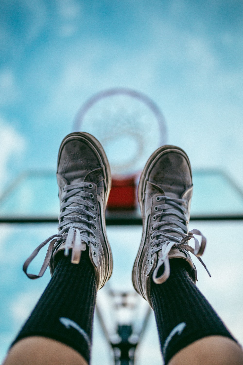 feet with dirty white basketball shoes raised into air under basketball hoop