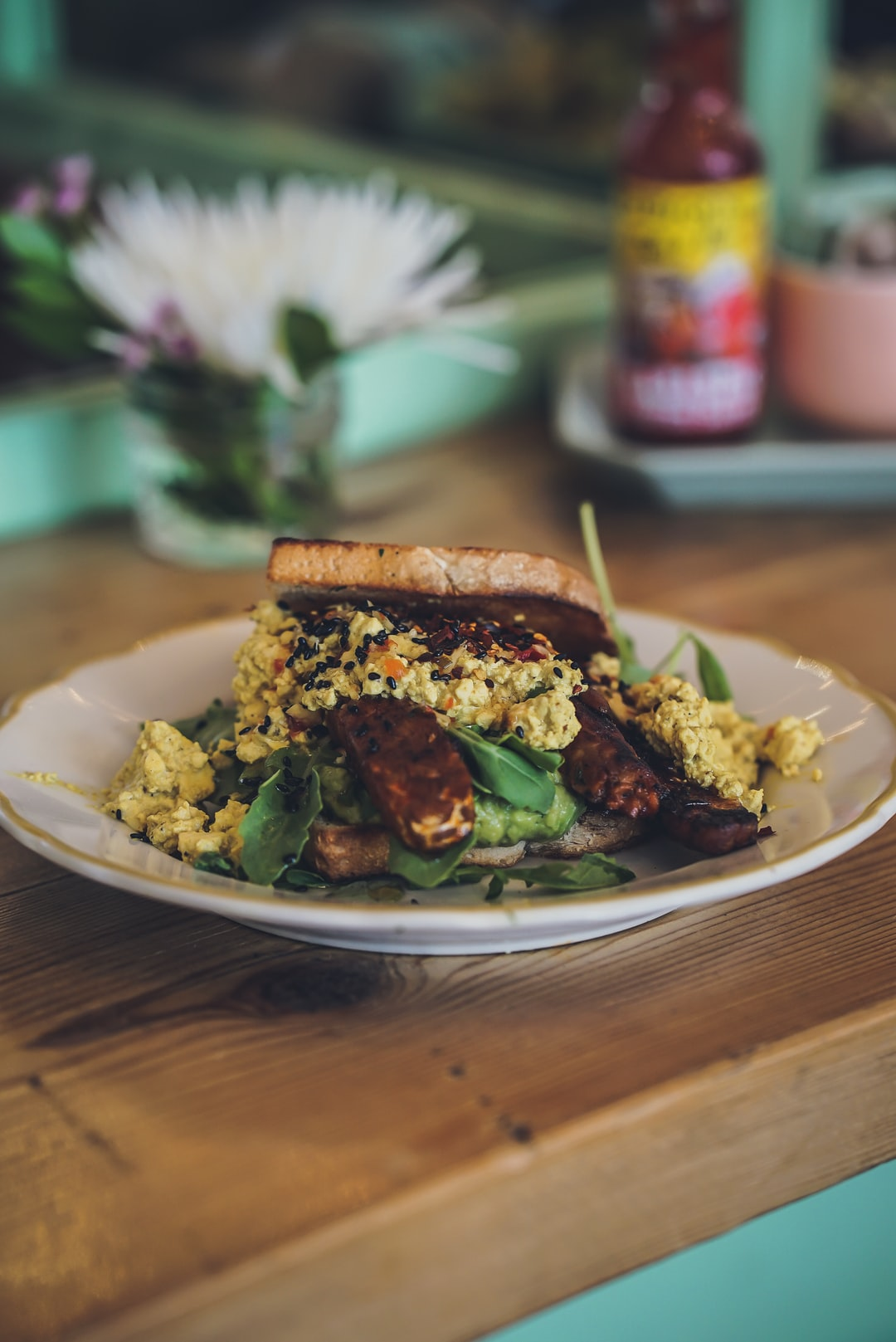 Eating a healthy vegan tempeh sandwich with scrambled tofu