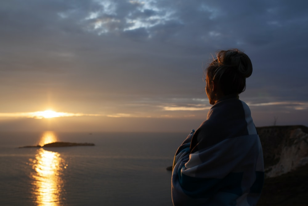 woman wrapped in blanket standing on higher ground watching sunset over the sea