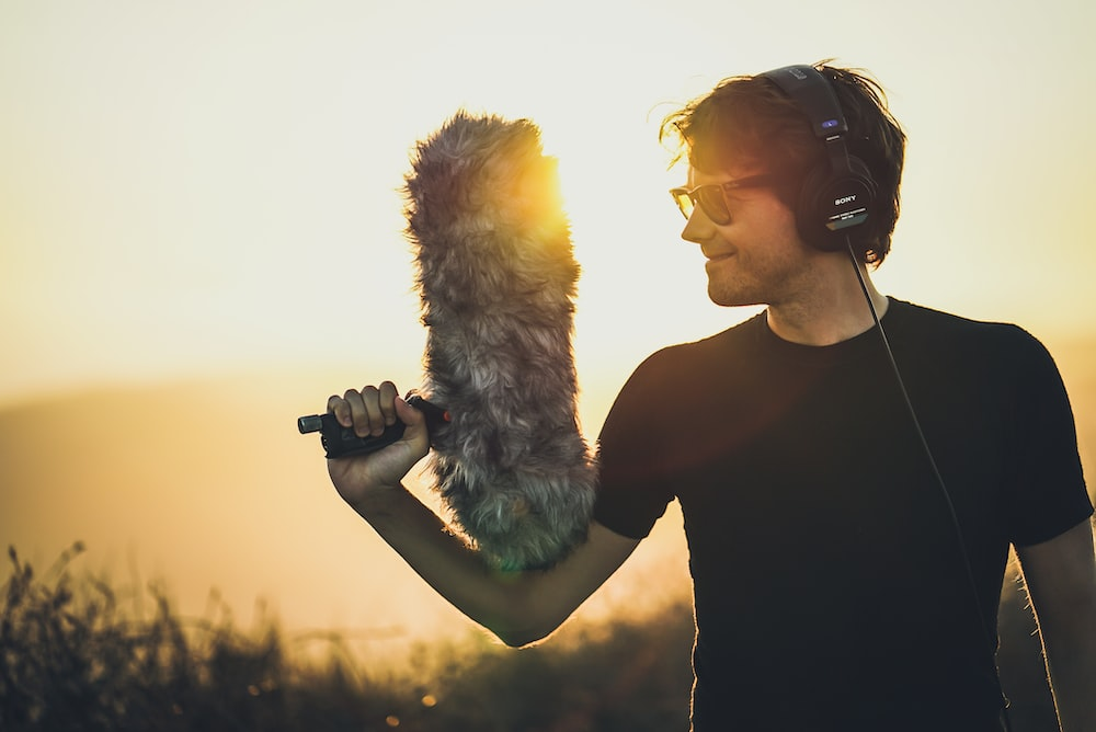 man smiling wearing headphones and holding fur microphone