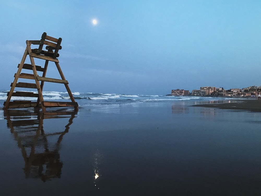 brown wooden chair on seashore