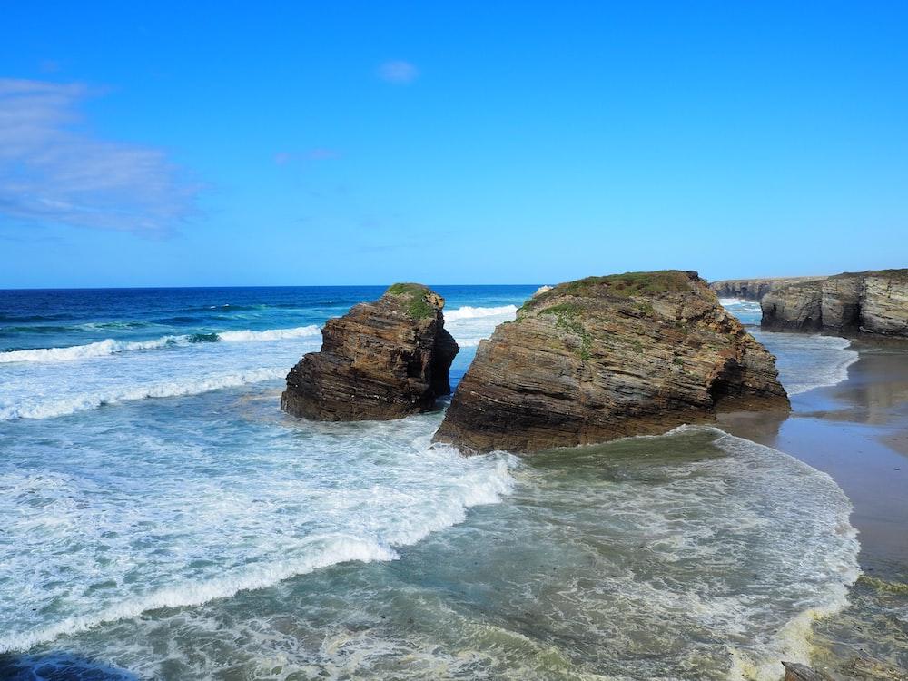 rocks near seashore viewing sea under blue and white skies