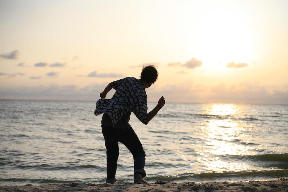 man about to throw stone on sea