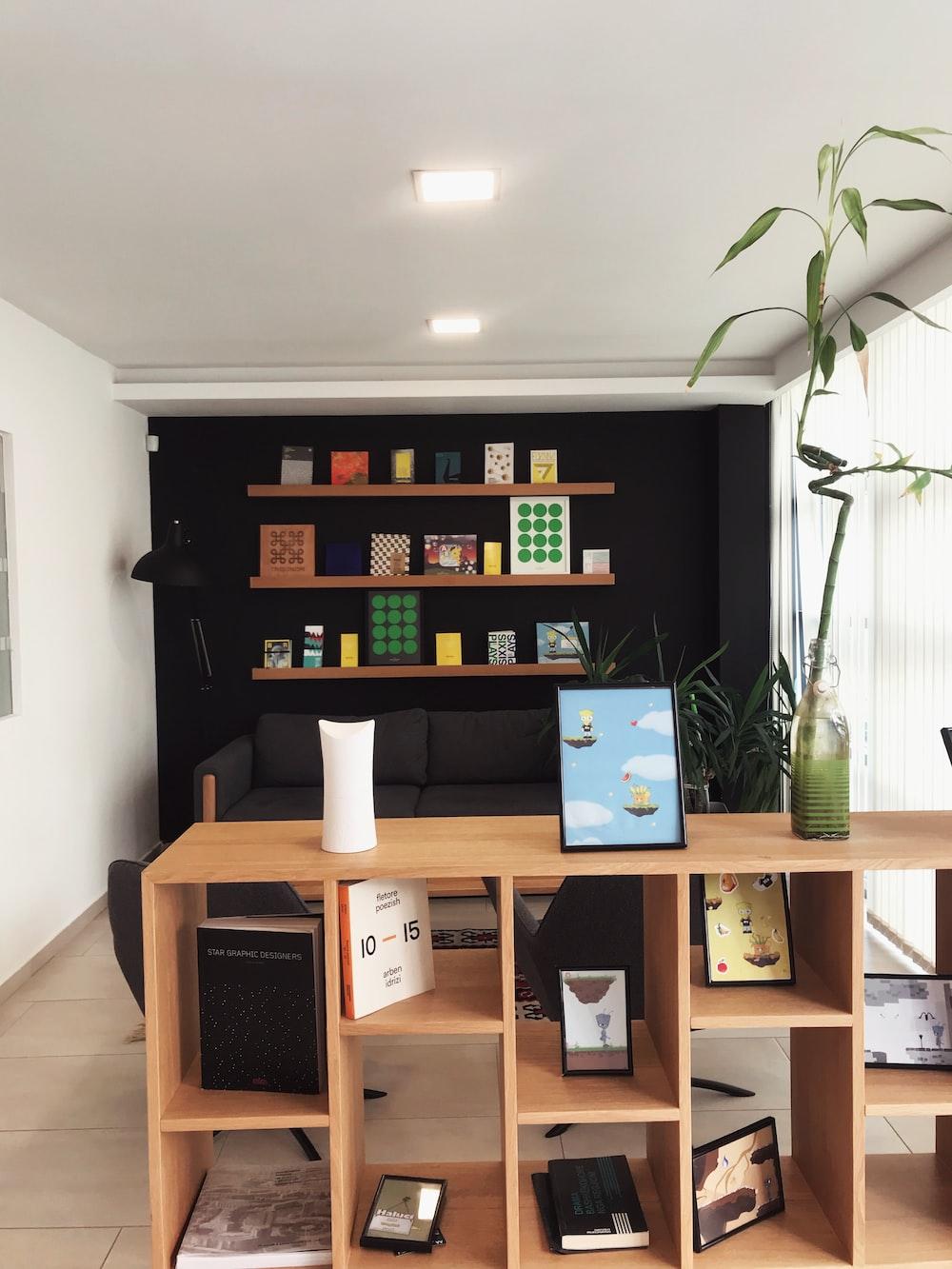 black iPad near lucky bamboo in vase on brown wooden shelf inside room