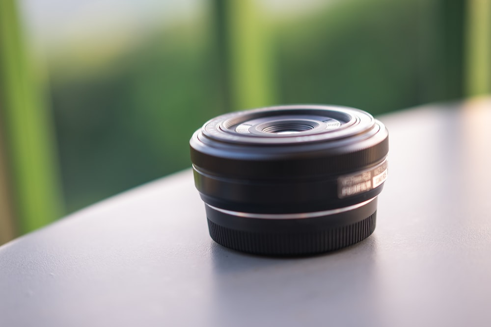 selective focus photography of round black lens on gray surface