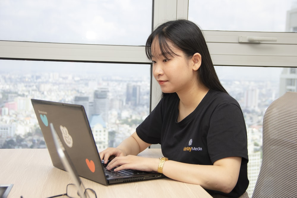 woman in black shirt using gray laptop computer