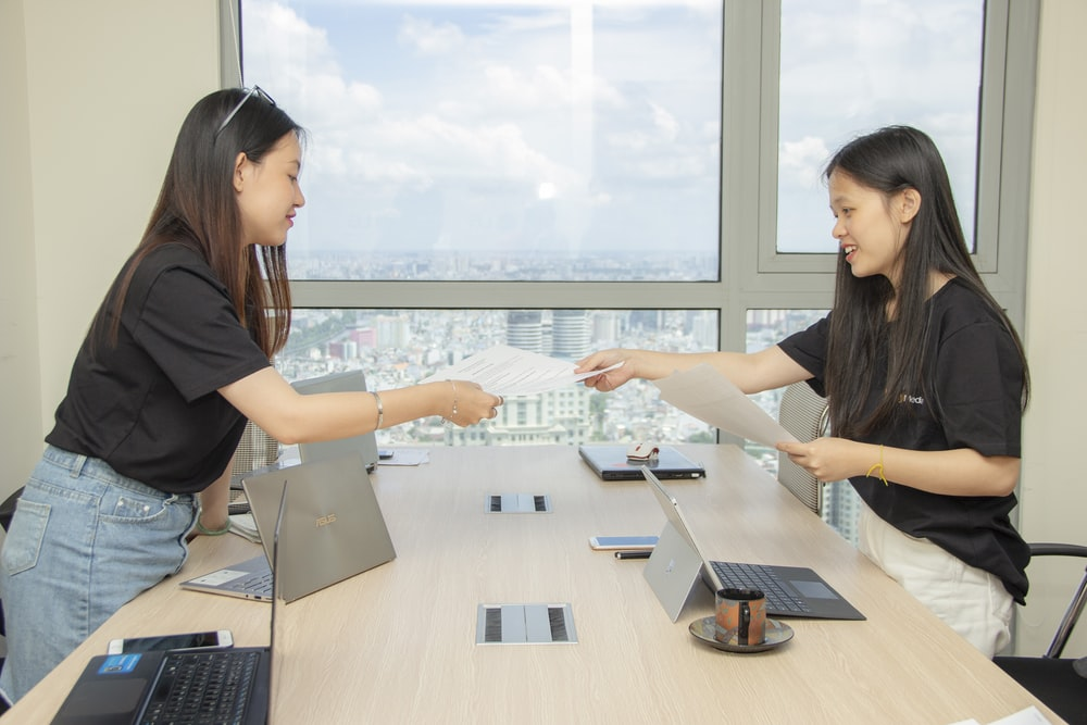two women standing by the conference table handing paper