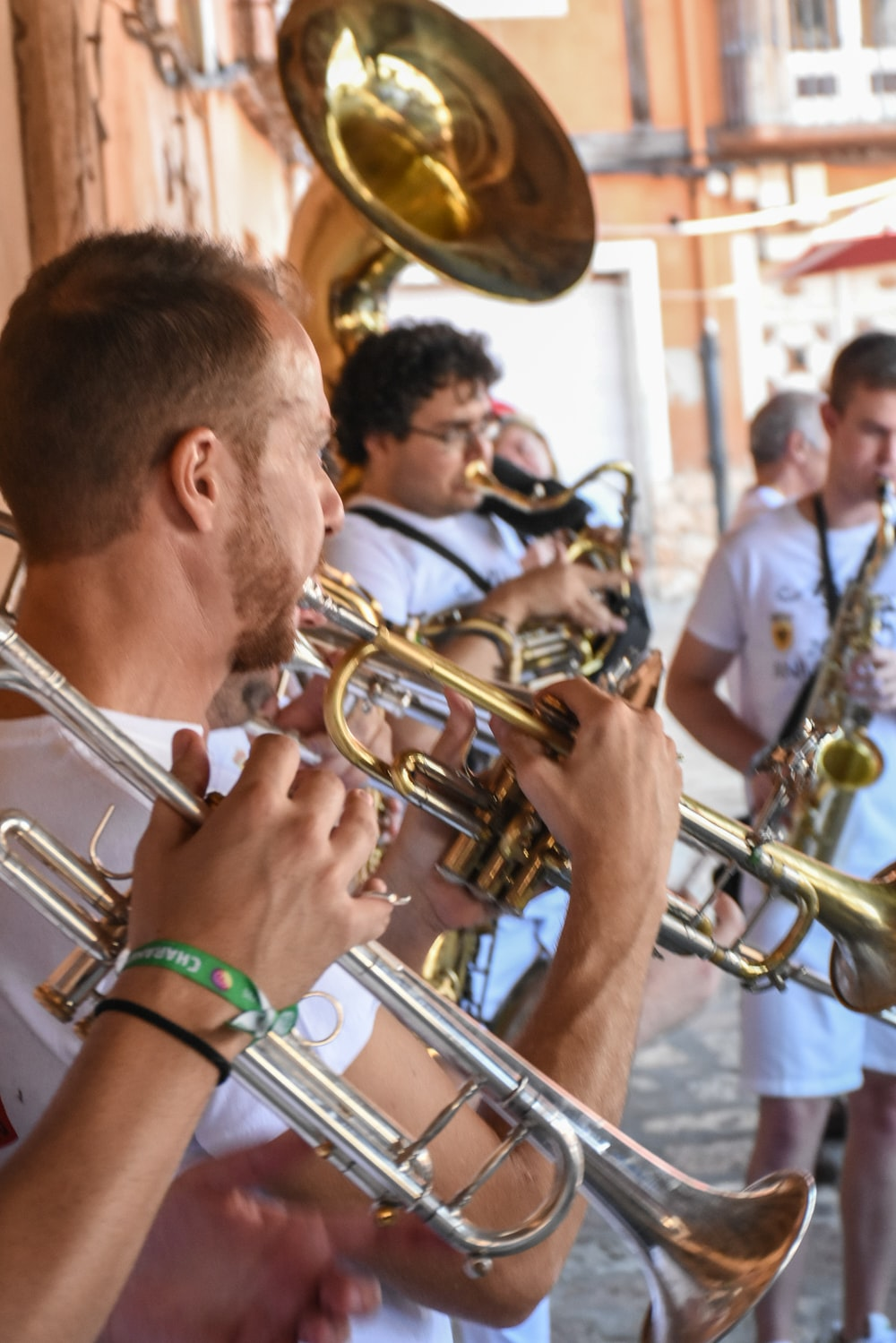 male band playing brass wind instrument outdoors