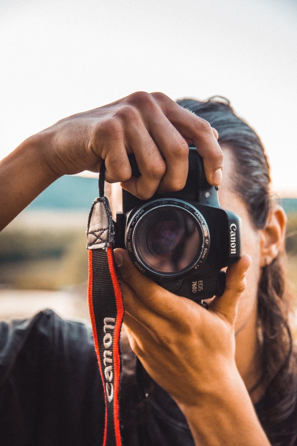 person holding black Canon camera close-up photography