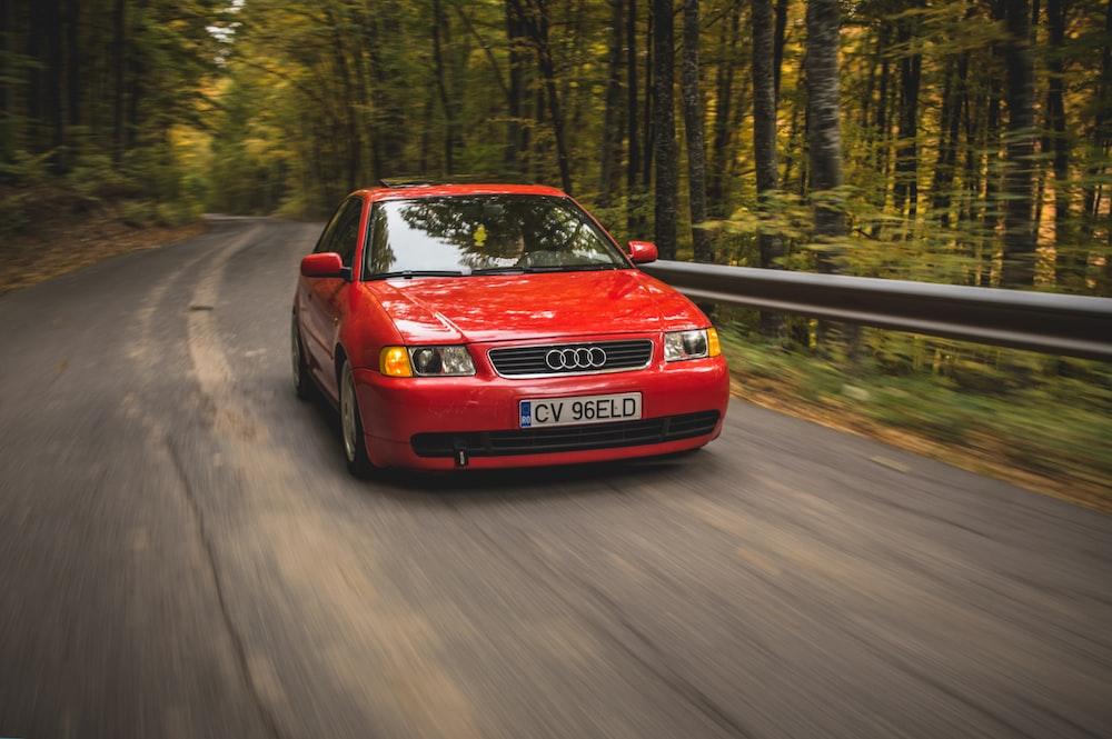 red Audi sedan passing on road between trees during daytime