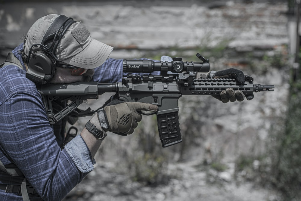 person holding black rifle close-up photography