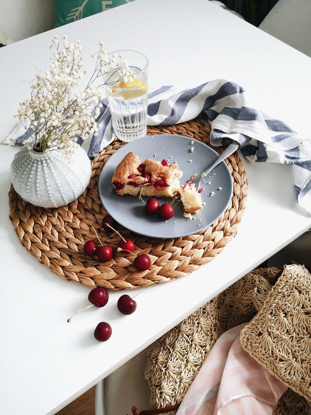 sliced pie with cherries in plate near water in glass on table