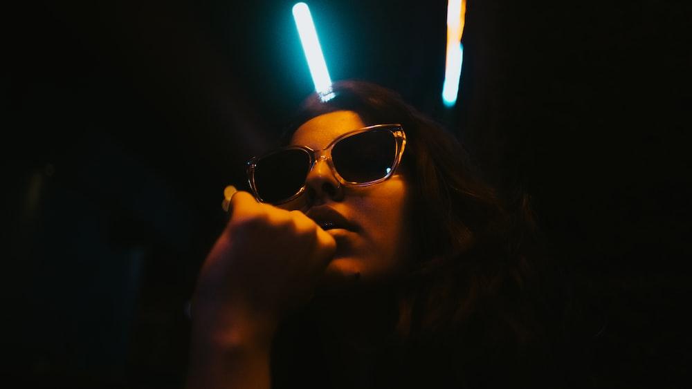 woman wearing sunglasses in dim light