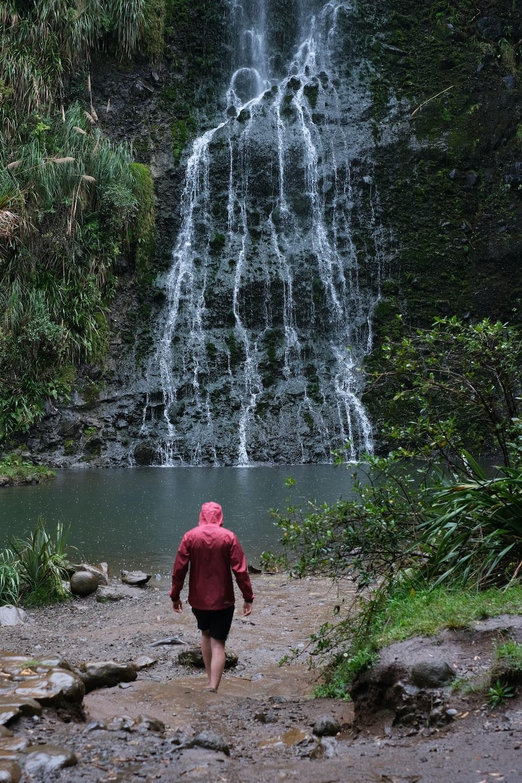 man walking towards a multi-tier waterfall