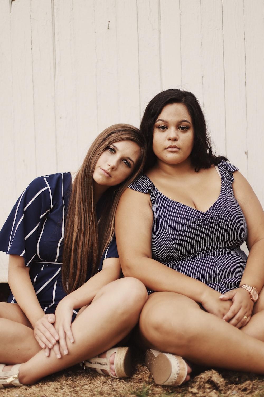 two women sitting on ground