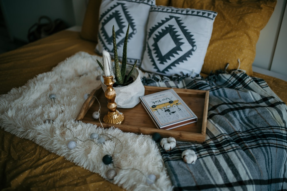 brown wooden tray on bed