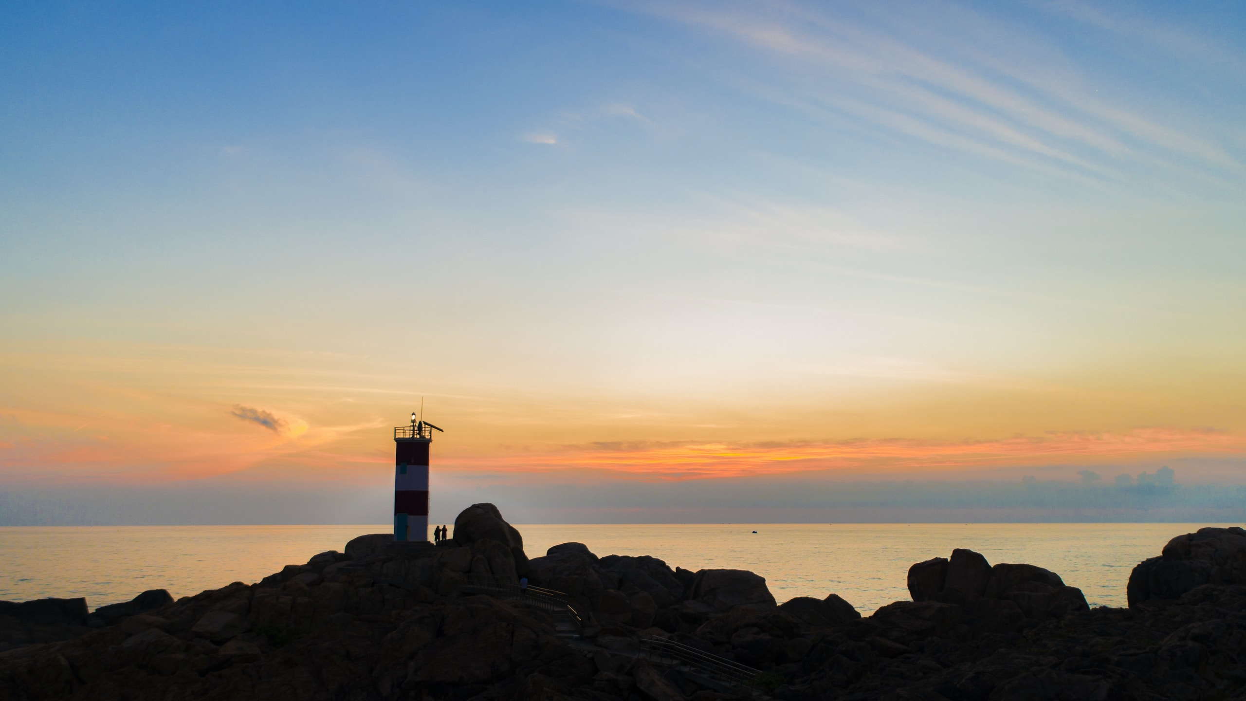silhouette photography of lighthouse by the sea during golden hour