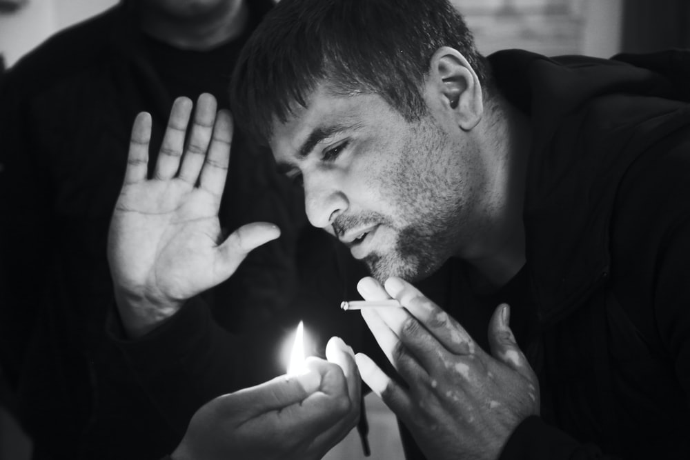 grayscale photo of man about to blow on flame