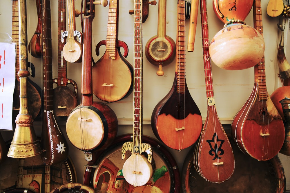 variety of brown wooden tribal stringed instruments displayed on wall