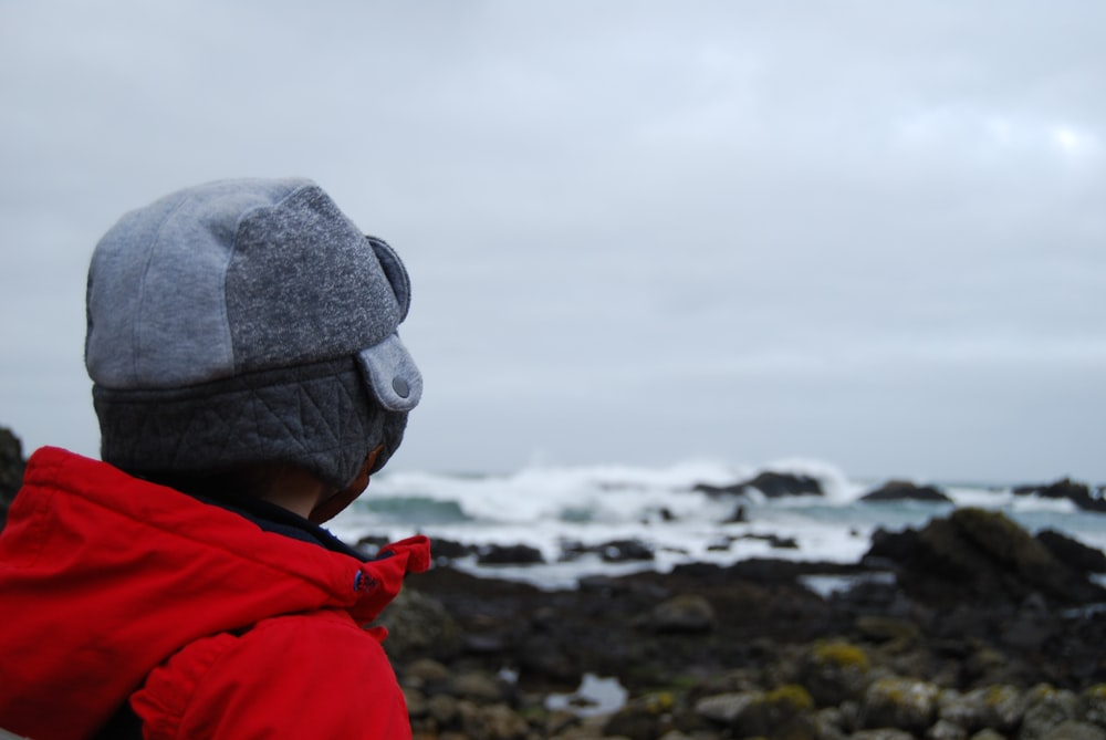 person wearing red hooded top facing the field of rocks and ocean
