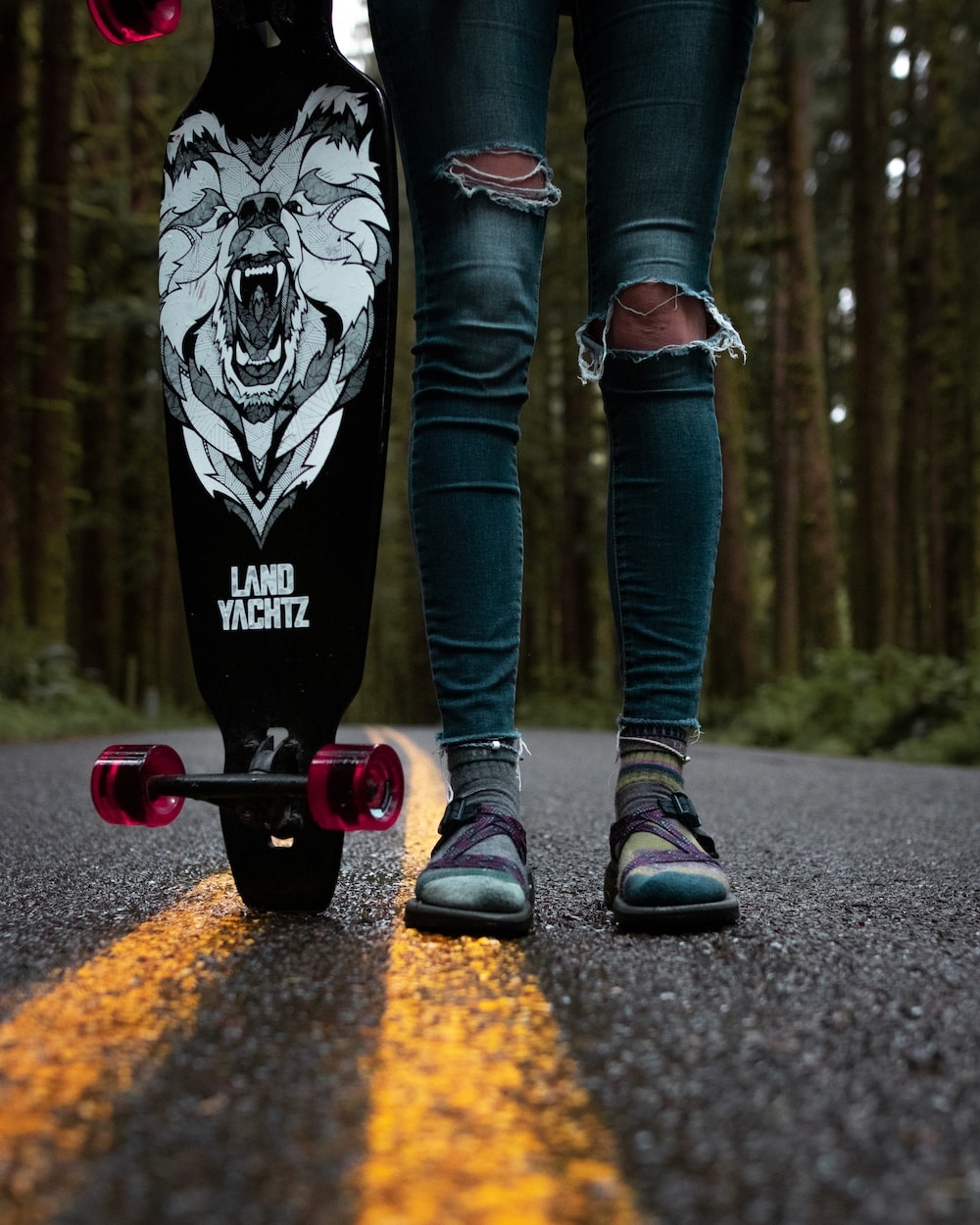 person standing and holding black and white skateboard
