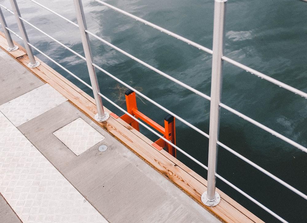 white metal rail beside body of water